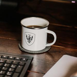 Eine Nahaufnahme von einer Kaffeetasse vor einer PC-Tastatur.