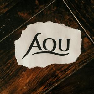 Ein Papierschnippsel mit den drei Buchstaben AQU.