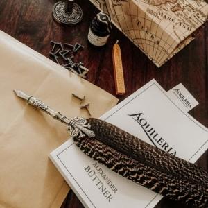 Eine Schreibfeder, ein Tintenfass, Siegelwachs und das Buch AQUILERIA Geschichten Band I.