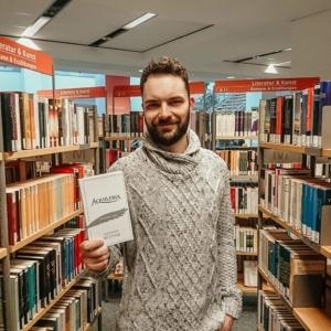 Eine Aufnahme von Alexander Büttner mit dem Buch AQUILERIA Geschichten Band I in der Chemnitzer Stadtbibliothek.