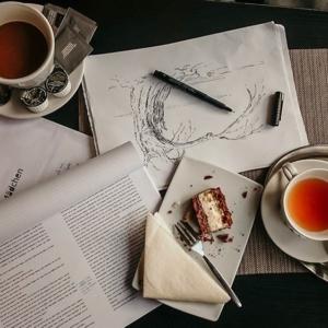 Eine Aufnahme von einem Manuskript, einer Skizze, Tee und Kuchen.