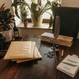 Eine Aufnahme von einem Tisch mit Versandtaschen, einer Schreibfeder und dem Buch AQUILERIA Geschichten Band I.