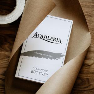 Eine Nahaufnahme des Buches AQUILERIA Geschichten Band I in Packpapier.