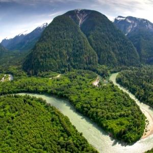 Ein Landschaftspanorama des Toba Valleys mit Bergmassiven im Hinter- und den waldigen Ufern des Flusses im Vordergrund.