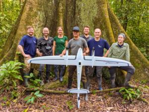 Das Team von Wilderness International mit einer Drohne vor einem großen Urwaldbaum.